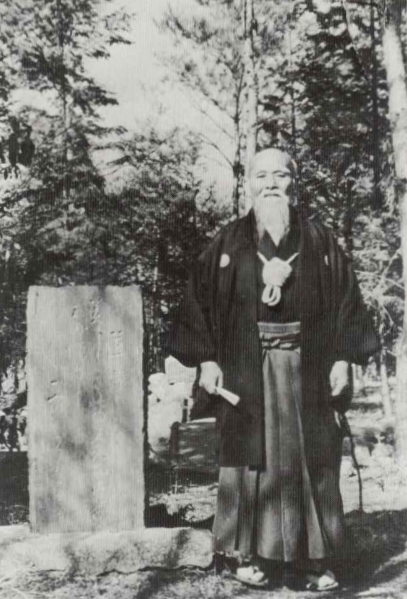 Morihei Ueshiba in Iwama next to one of his Doka