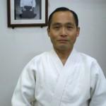 Tsuneo Ando, in front of Gozo Shioda's photograph